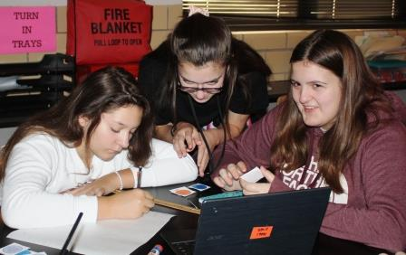 Eighth-grade students work together on a project in their advanced Earth & Space Science course.
