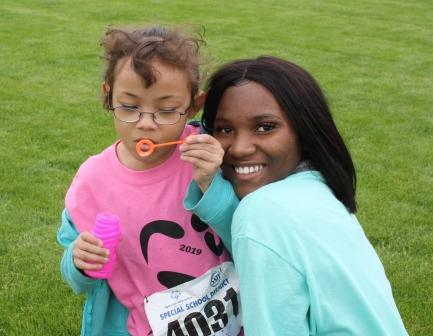RHS sophomore Moriah Yisrael, a first-time volunteer at Special Olympics, stops for a photo with her buddy.